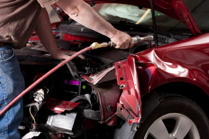 Auto Body Mechanic Disassembling Damaged Vehicle