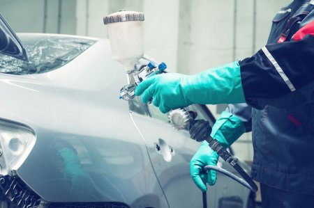 A professional coating the car with paint to remove scratches