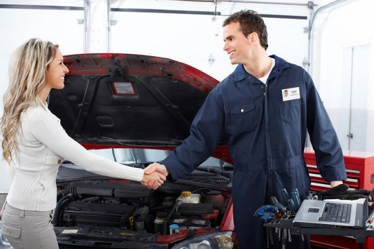 A woman and a professional car servicer shaking hands