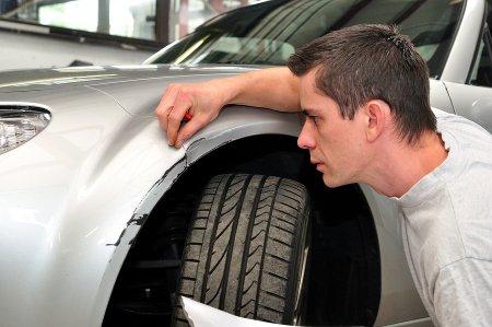 A boy checking the car