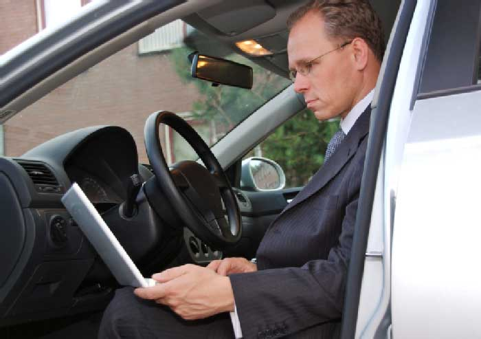 Businessman checking mail in the car