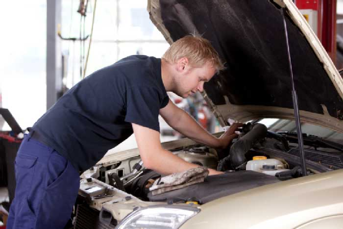 technician looking under hood