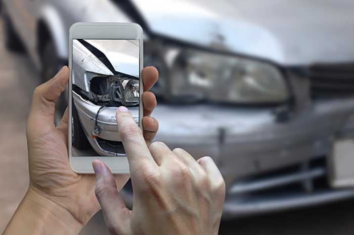Hand holding smart phone take a photo at The scene of a car crash, car accident for insurance