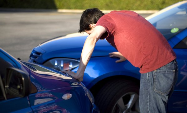 A man looking at the damage after collision with another car