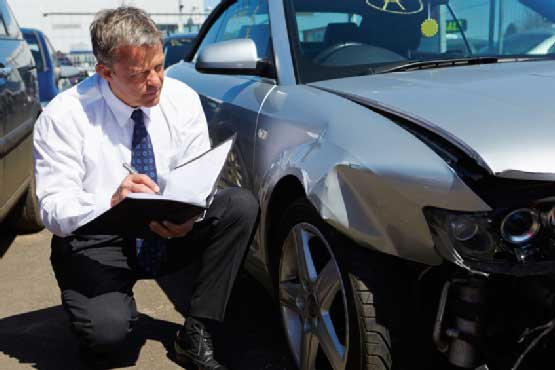 Man is looking at the car dent and noting down the details