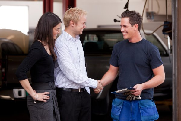 Happy Customer greeting the technician at an auto shop.