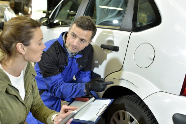 A technician and a customer discussing about body paint of the car