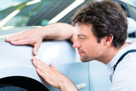 Man checking the dent of a car