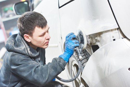 Mechanic repairing the bumper of car