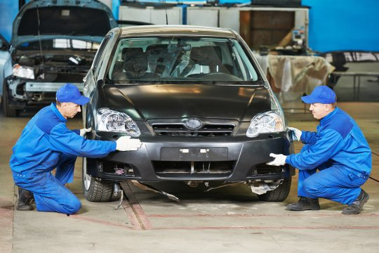 Mechanics replacing bumper of the car