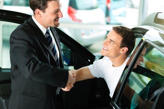 A dealer cracking a car deal with a client